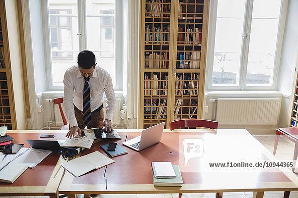 Männliche Anwälte recherchieren am Tisch in der Bibliothek