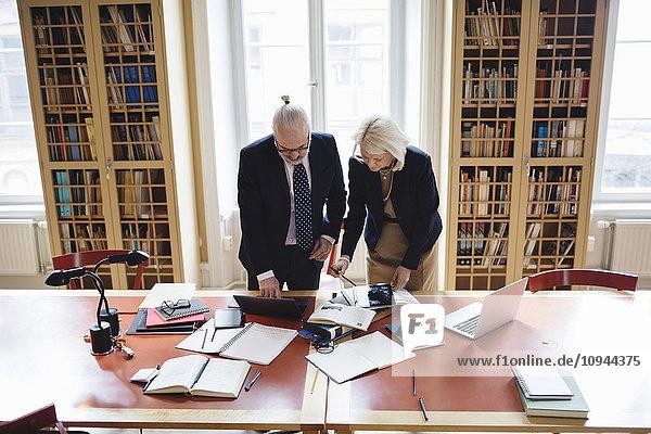 Hochauflösender Blick auf ältere Anwälte,  die Technologien am Tisch in der Bibliothek nutzen.