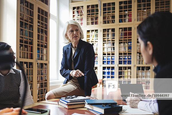 Ältere professionelle Gestik während der Sitzung auf dem Tisch in der Bibliothek
