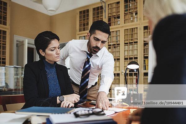 Rechtsanwältin im Gespräch mit Mitarbeiterinnen am Tisch in der Sitzung