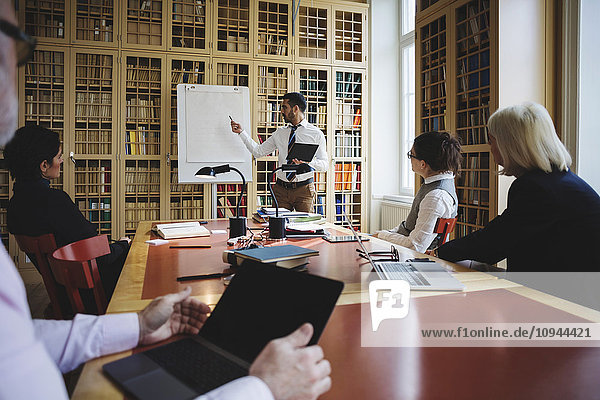 Männlicher Fachmann bei der Präsentation vor Mitarbeitern im Sitzungssaal