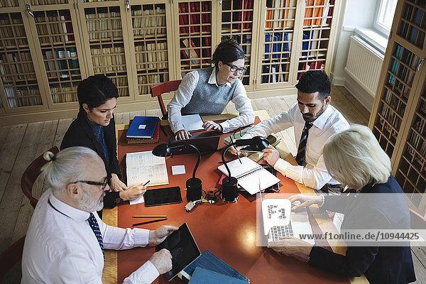 Hochwinkelansicht von Fachleuten  die am Tisch in der Rechtsbibliothek arbeiten
