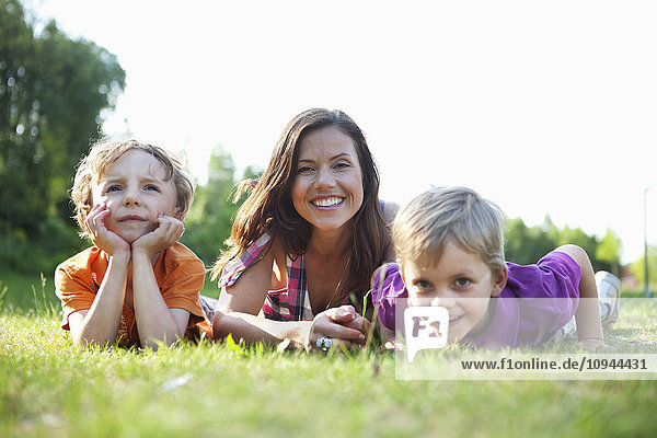Portrait of a happy mother and children lying on grass
