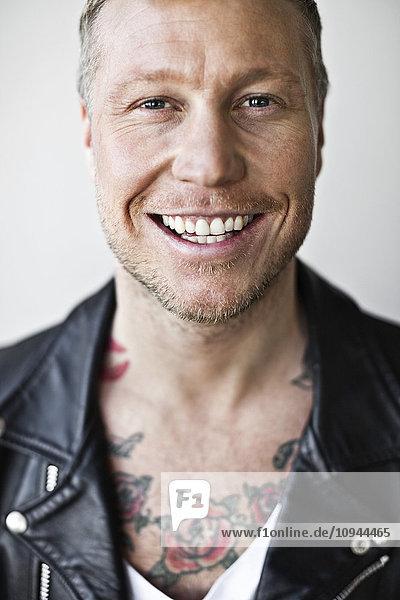 Nahaufnahme eines glücklichen erwachsenen Mannes  der über grauem Hintergrund lächelt