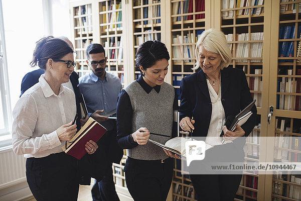 Lächelnde Anwälte diskutieren bei einem Spaziergang durch das Bücherregal in der Bibliothek