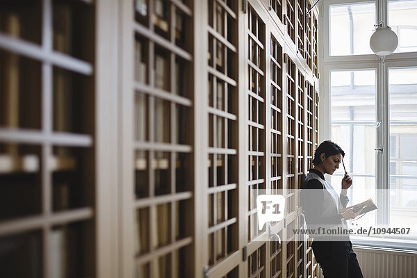 Nachdenkliche Anwältin recherchiert  während sie sich in der Bibliothek auf das Regal stützt.