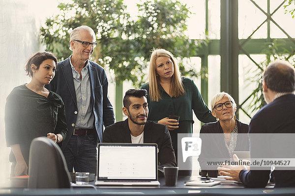 Multiethnische Geschäftsleute hören dem Manager im Kreativbüro zu.
