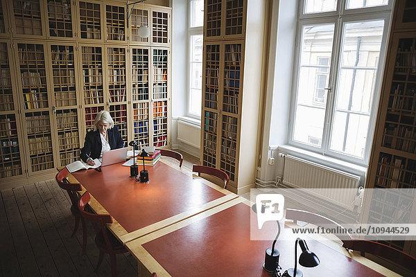 Seniorin recherchiert am Tisch in der juristischen Bibliothek