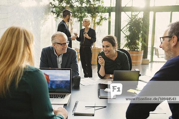 Lächelnde Geschäftsfrau im Gespräch mit Kollegen im Kreativbüro