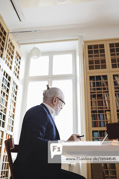 Niedriger Blickwinkel auf einen älteren Anwalt in der Bibliothek