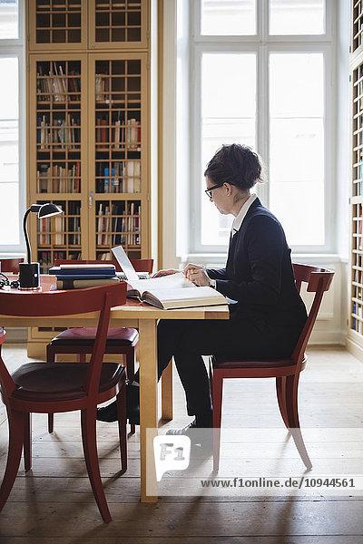 Anwältin mit Laptop bei Tisch in der Bibliothek