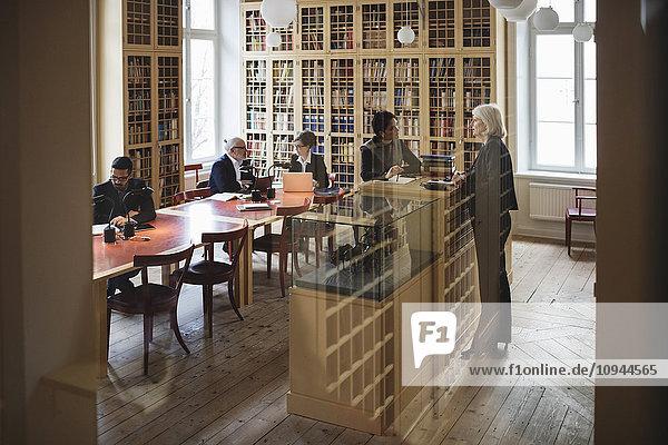 Rechtsanwälte in der Bibliothek gesehen durch Glas in der Bibliothek
