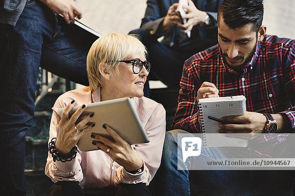 Geschäftsleute mit Notizblock und digitalem Tablett auf Stufen im Büro sitzend