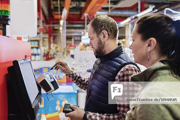 Mann  der mit Kreditkarte bezahlt  während er mit einer Frau im Supermarkt steht.