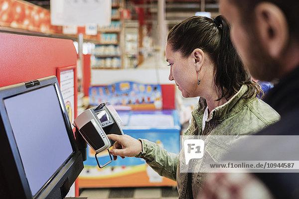 Weibliche Kundin  die mit einem Mann im Supermarkt steht und bezahlt