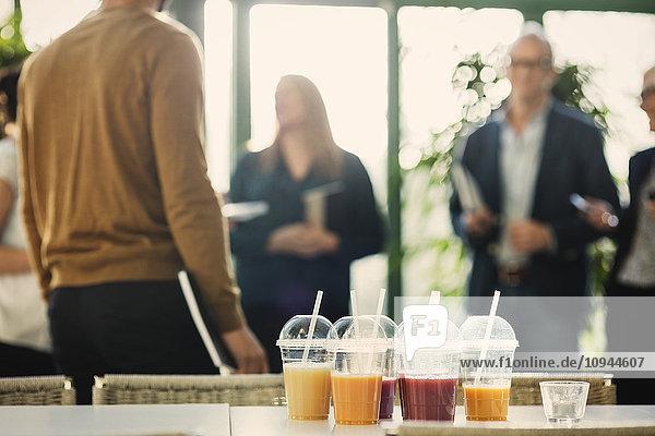 Fruchtsaft in Plastikbechern auf dem Tisch mit Geschäftsleuten im Hintergrund im Büro