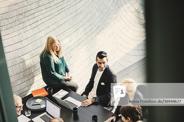 Hoher Blickwinkel des jungen Geschäftsmannes mit Kollegen im Kreativbüro
