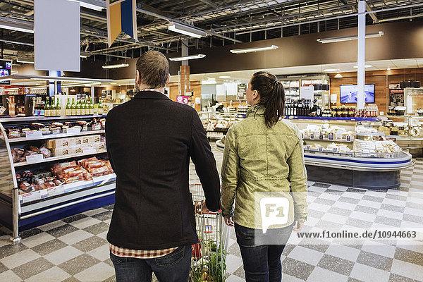 Rückansicht des Paares mit Einkaufswagen im Lebensmittelgeschäft