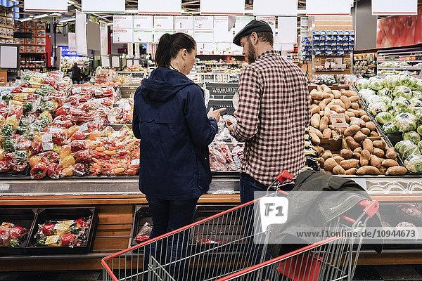 Rückansicht des Paares  das im Supermarkt steht und Gemüse auswählt.