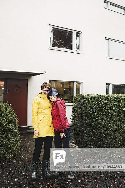 Porträt eines lächelnden lesbischen Paares im Regenmantel vor dem Haus stehend