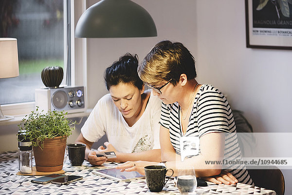 Lesbian couple using digital tablet while sitting at dining table