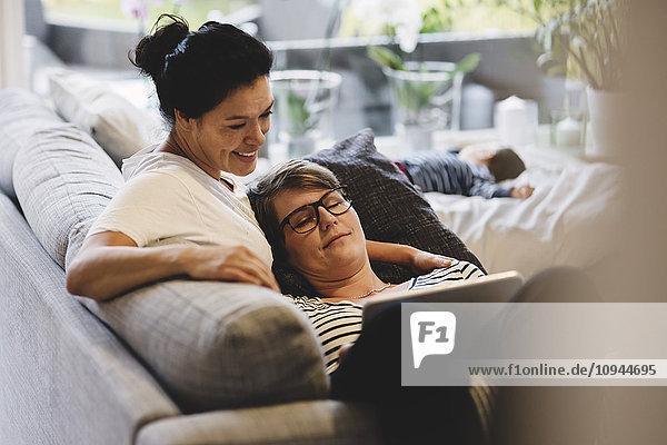 Lächelndes lesbisches Paar  das sich umarmt  während es die Tafel im Wohnzimmer zu Hause betrachtet.