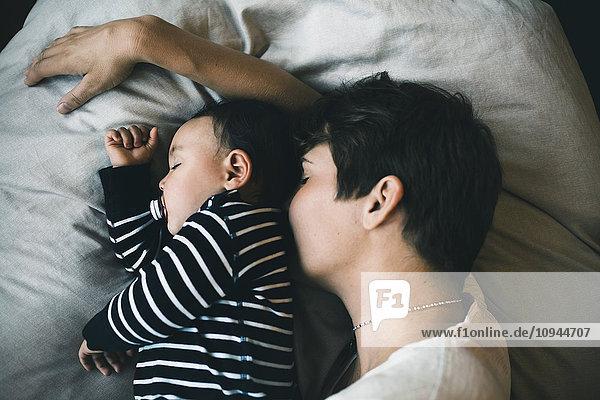 Hochwinkelansicht von Mutter und Kleinkind  die zu Hause auf dem Bett schlafen Hochwinkelansicht von Mutter und Kleinkind, die zu Hause auf dem Bett schlafen