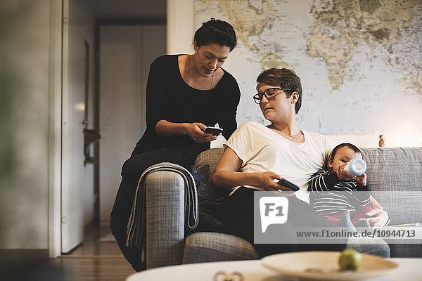 Frau zeigt der Mutter das Telefon  während das Kleinkind Milch aus der Flasche trinkt.