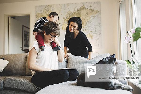 Mutter mit Tochter beim Betrachten des digitalen Tabletts mit Frau zu Hause
