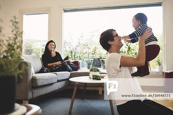 Lächelnde Frau  die die Mutter beim Spielen mit der Tochter im Wohnzimmer ansieht.
