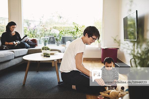 Mutter und Tochter spielen mit Spielzeug  während die Frau zu Hause ein digitales Tablett benutzt.