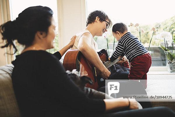Frau sieht lächelnde Mutter und Tochter  die zu Hause Gitarre spielen