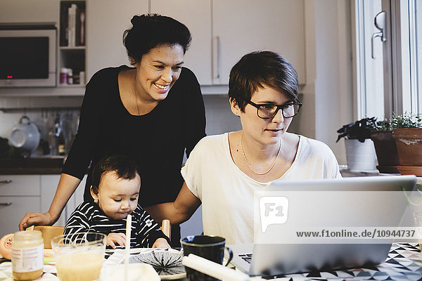 Frauen  die im Laptop schauen  während das kleine Mädchen am Tisch isst.