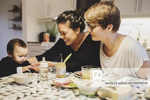 Glückliches Paar füttert Kleinkind am Esstisch