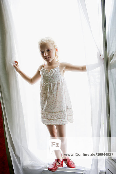 Girl standing in front of white curtain