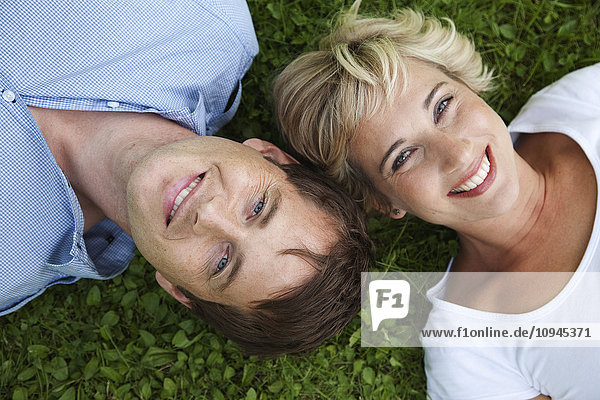 Sweden  Stockholm  portrait of couple lying on grass