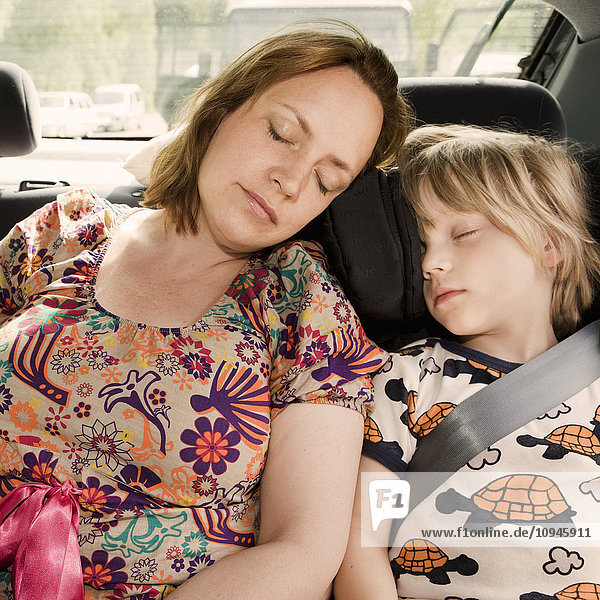Mother and son sleeping inside car