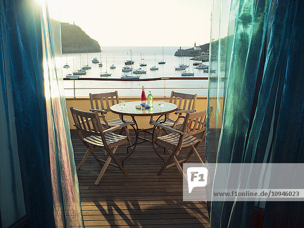 Wooden table and chairs with sea in background Wooden table and chairs with sea in background