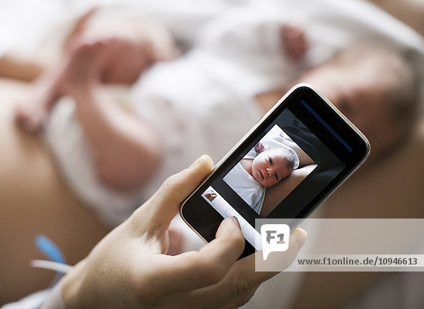 Mother taking photograph of baby using mobile phone