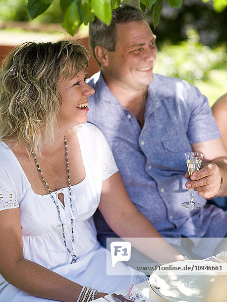 Man and woman having drink in garden