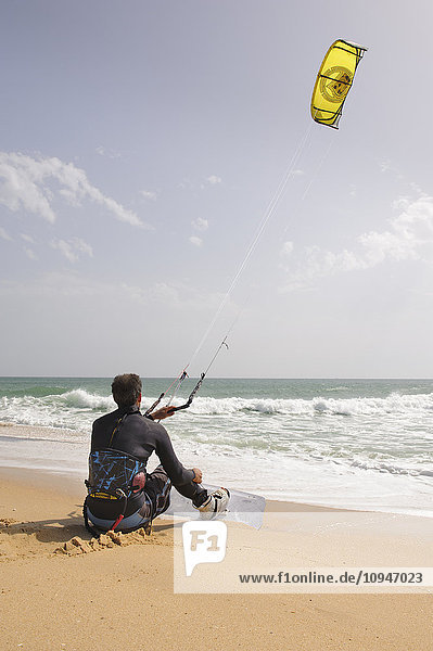 Paraglider sitting on beach waiting to take off