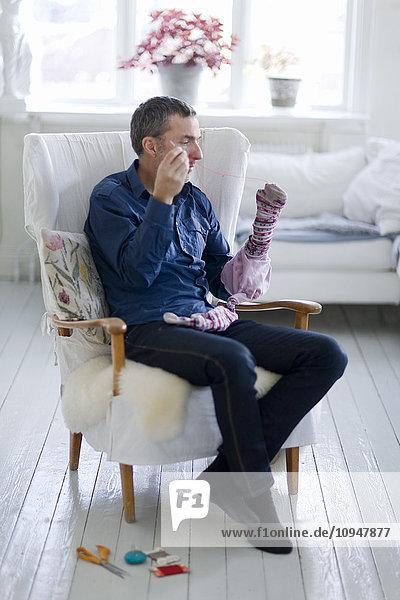Mature man sewing stockings