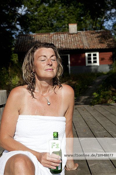 Woman wrapped in towel relaxing on deck