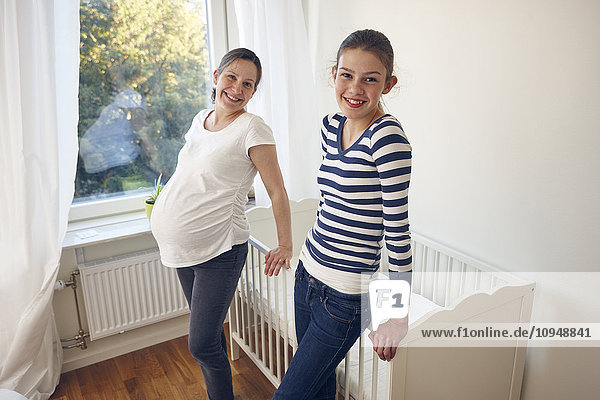 Mother with daughter standing near cot