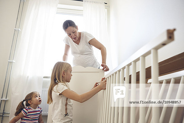 Mother and daughters building cot
