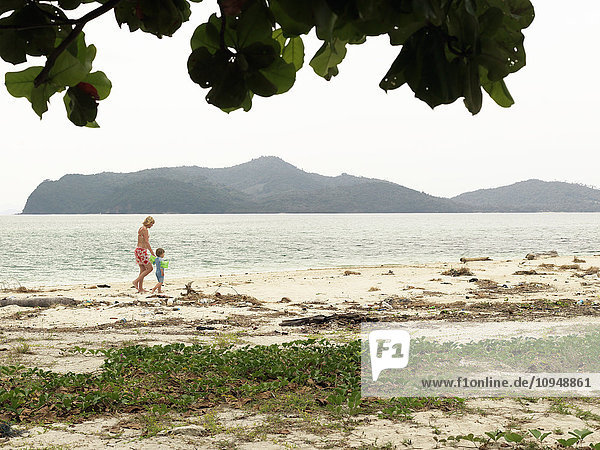Mother with son walking on beach