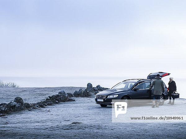 Couple near car at coast