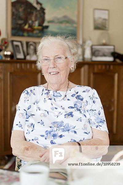 Portrait of senior woman sitting in living room