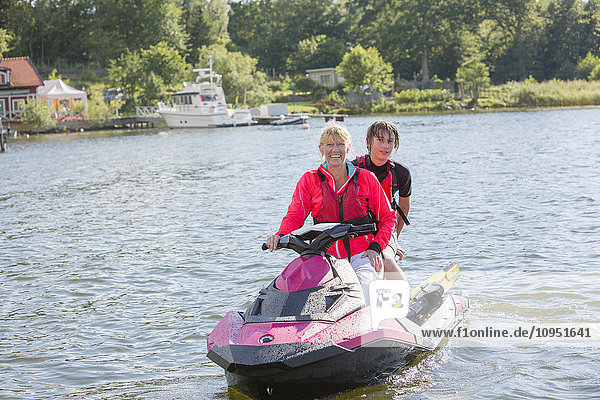 Mother and teenage son on jet ski