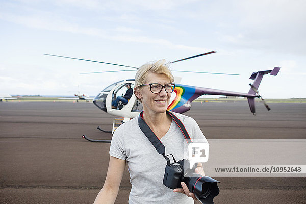 Smiling woman in front of helicopter